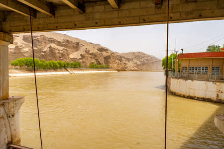 Karakash Black Jade River Dam View of the Streaming Water on a Sunny Blue Sky Day 写真素材