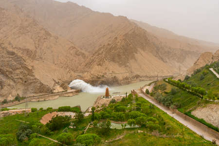 Hotan Wuluwati Hydroelectric Power Generation Dam High Angle View of the Released River Stream and Pagoda on a Foggy Day Stock fotó