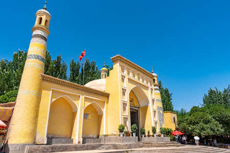 Kashgar Id Kah Mosque with a Waving China Flag on the Top of the Roof and Chinese Tourists on a Sunny Blue Sky Day