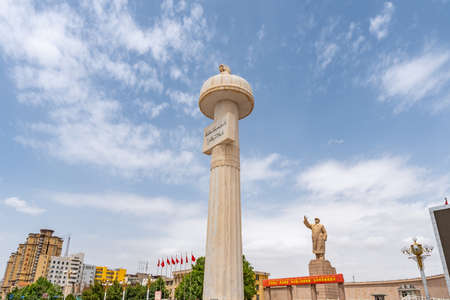 Kashgar Stone Pillar with Uyghur Inscription with Mao Zedong Statue at People's Park Square on a Sunny Blue Sky Day Stock Photo