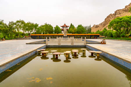 Hotan Wuluwati Hydroelectric Power Generation Dam View of Yu the Great Statue at a Pond on a Foggy Day 写真素材