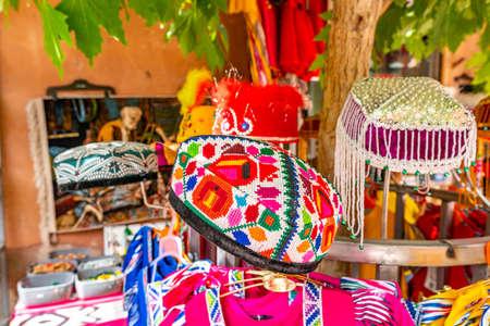 Sombreros doppa uigur tradicionales de Kashgar en varios colores para niñas en una tienda de ropa
