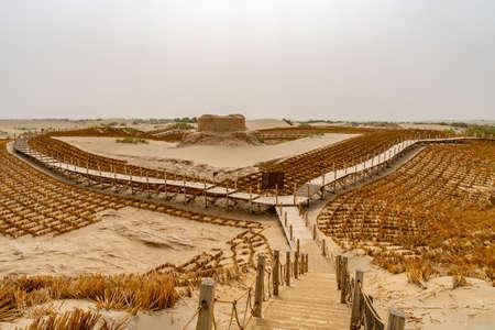 Hotan Rawak buddhistische Stupa-Ruinen in Xinjiang Taklamakan Wüstenansicht mit Holzsteg an einem sonnigen bewölkten Tag
