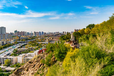 Urumqi Hong Shan Red Mountain Park with Lin Zexu Statue and Cityscape at Background on a Sunny Blue Sky Day Редакционное