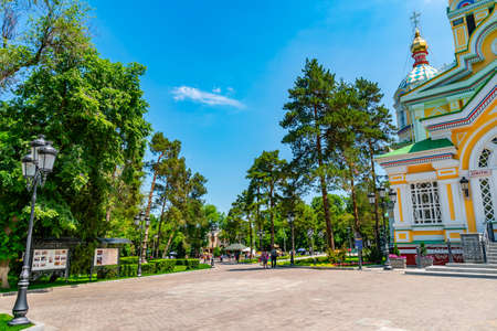 Almaty Russian Orthodox Christian Zenkov Ascension Cathedral of the Lord Road View with Walking People in Panfilov Park on a Sunny Blue Sky Day