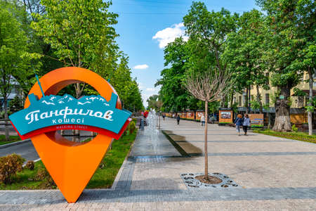 Almaty Panfilov Walking Street with Pin Pointing Road Sign and Strolling Young People on a Sunny Cloudy Blue Sky Day