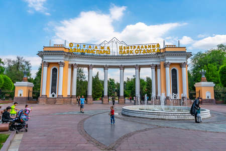 Almaty Central Park Main Gate Entrance Frontal View with Fountain and Visitors on a Sunny Cloudy Blue Sky Day