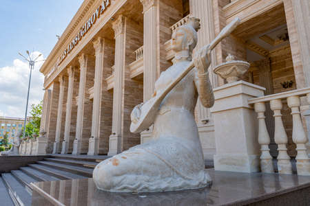 Taldykorgan Zhansugurov Palace of Culture Building Picturesque View with a Woman Statue Playing Guitar on a Sunny Blue Sky Day 免版税图像