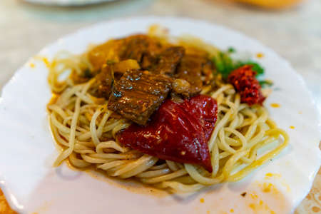 Traditional Mouthwatering Central Asian Uyghur Fried Noodles Lagman Dish with Vegetables on a White Plate Stock Photo