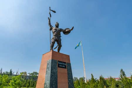 Taraz Presidential Park Statue of Koshek Batyr Holding a Spear with Huge Waving Kazakhstan Flag at Background on a Sunny Blue Sky Day