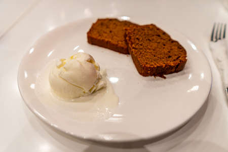 Traditional French Soft Chocolate Cake with a Scoop of Vanilla Ice Cream on a White Plate