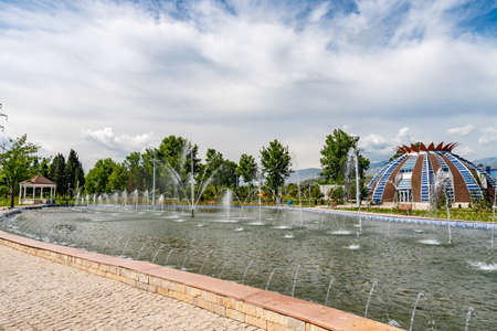 Dushanbe Youth Park Picturesque View of Pomegranate Shaped House and Pond with Fountains on a Sunny Blue Sky Day