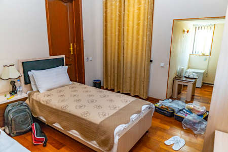 Hotel Comfortable Clean Double Bedroom with Beige Colored Curtain Linen with Wooden Floor