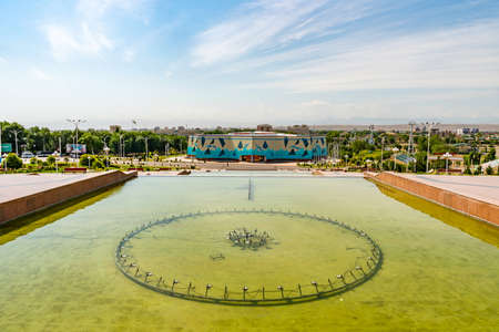Khujand Ismoil Somoni Park View of 20 Year Anniversary of Tajikistan Independence Indoor Swimming Pool Building and Fountain on a Sunny Blue Sky Day