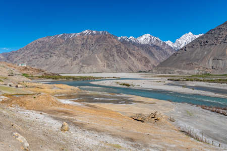 Pamir Highway Wakhan Corridor View with Panj River Valley and Afghanistan Snow Capped Mountains on a Sunny Blue Sky Day Standard-Bild