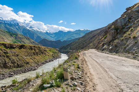 Qalai Khumb to Khorog Pamir Highway Picturesque Panj River Valley View of Snow Capped Mountains on a Sunny Blue Sky Day