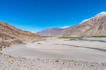 Pamir Highway Wakhan Corridor View mit Panj River Valley Desert und Afghanistan schneebedeckten Bergen an einem sonnigen blauen Himmelstag?