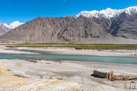 Pamir Highway Wakhan Corridor View of a Hut with Panj River Valley and Afghanistan Snow Capped Mountains on a Sunny Blue Sky Day Standard-Bild