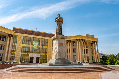 Khujand Cultural Palace Sugdiyon with View of Abu Abdullah Rudaki Statue on a Sunny Blue Sky Day