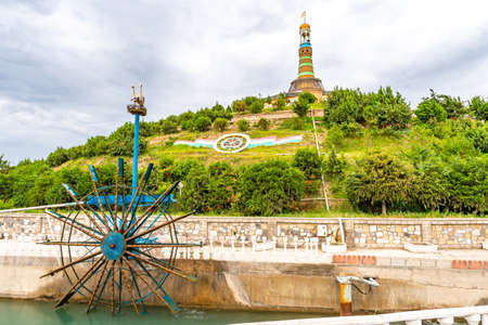Qurghonteppa Bokhtar Bibikhonum Teppa Modern History Museum Monument with Waving Tajikistan Flag and Water Wheel on a Cloudy Rainy Day Редакционное