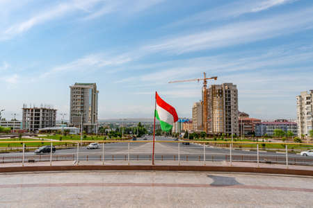 Khujand Waving Tajikistan Flag at Stella Ring Road and Ismoil Somoni Avenue Prospekt on a Sunny Blue Sky Day Редакционное