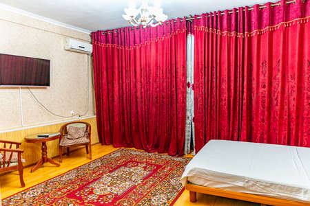 Hotel Simple Clean Double Bedroom with Red Colored Curtain and Table with Chairs