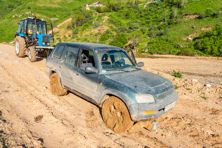 Khoburobot Pass from Qalai Khumb to Dushanbe Tractor Pulls out SUV Jeep Stuck from Mud Slide on a Sunny Blue Sky Day