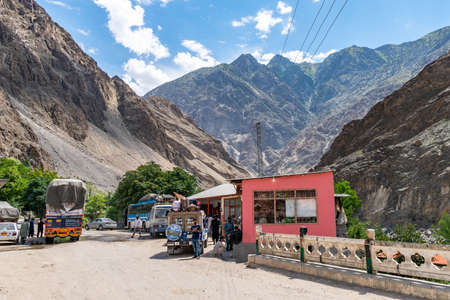 Gillgit to Skardu Sassi Village with Parked Vehicles People and Open Grocery Shops on a Sunny Blue Sky Day