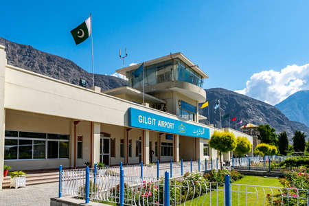 Gilgit Domestic Airport Air Traffic Control Tower with Waving Pakistan Flag on a Sunny Blue Sky Day