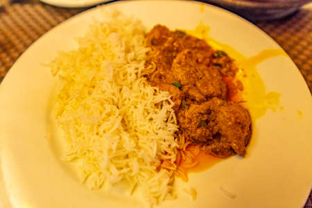 Traditional Mouthwatering Pakistani Orange Colored Spicy Lamb Curry Served with Rice Imagens