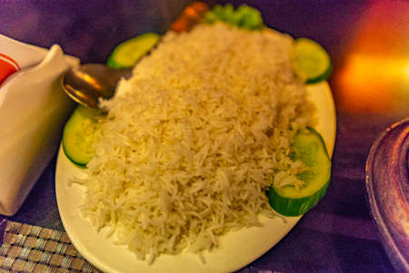 Traditional Mouthwatering Pakistani Heap of Rice Served on a White Plate with Cucumber