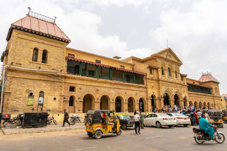 Karachi Main Railway Cantonment Station Picturesque View with Passing People and Rickshaws on a Cloudy Day