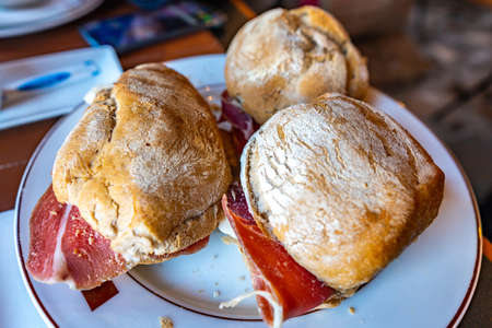 Three Traditional Mouthwatering Portuguese Pork Ham and Sheep Cheese Sandwiches on a White Plate