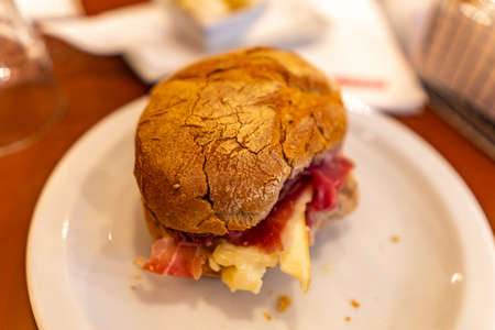 Traditional Mouthwatering Portuguese Pork Ham and Sheep Cheese Sandwich on a White Plate