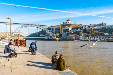 Porto Luis I Bridge Breathtaking Picturesque View with Seagulls and Sitting People at the Shore on a Blue Sky Day in Winter