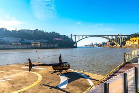Porto Picturesque View of a Helitours Helicopter with Arrabida Bridge on a Sunny Blue Sky Day in Winter