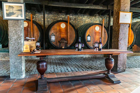 Porto Croft Port Wine Cellar Picturesque Interior View of Wine Barrels and a Table with Alcohol and Glasses