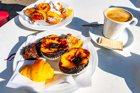 Traditional Mouthwatering Tasty Portuguese Pastel de Nata and Various Bakery Sweets on White Plates with Galao Coffee