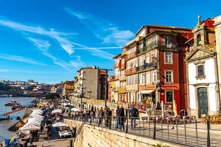 Porto Ribeira Square Breathtaking Picturesque View with Walking People and Anchored Ships on a Sunny Blue Sky Day in Winter