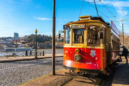 Porto Man Enters Red Colored Retro Tramway Picturesque View at Rua Nova da Alfandega Street on a Sunny Blue Sky Day in Winter
