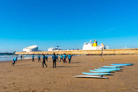 Porto Praia de Matosinhos Beach Picturesque View with Surfers and Leixoes Harbor Port on a Sunny Blue Sky Day