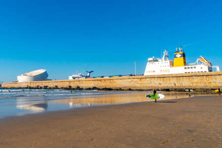 Porto Praia de Matosinhos Beach Lone Surfer Picturesque View with Leixoes Harbor Port on a Sunny Blue Sky Day