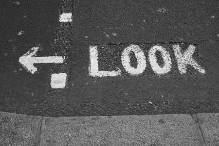 Look word with arrow written on road photo