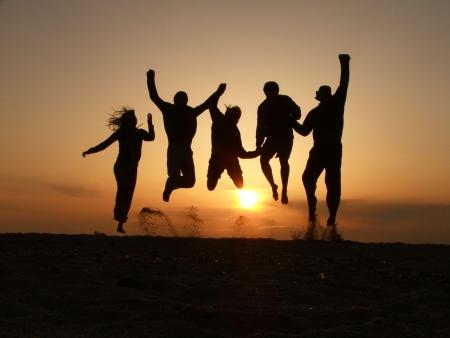 donna entusiasta: tramonti amici saltando sulla spiaggia