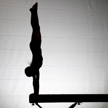 beam: silhouette of gymnast on balance beam