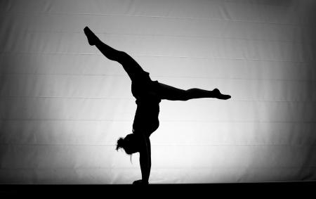 somersault: silhouette of gymnast on balance beam