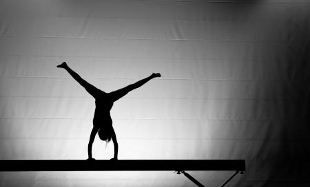 young gymnast: silhouette of gymnast on balance beam