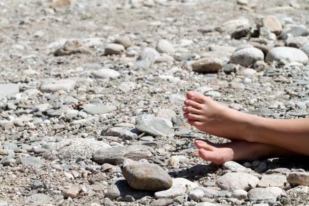 石のビーチで太陽の下でフィート 写真素材