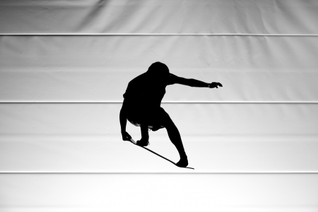 acrobatic: silhouette with board on trampoline Stock Photo
