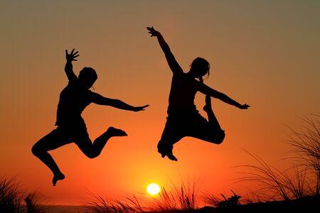 free running: sunset girls jumping Stock Photo